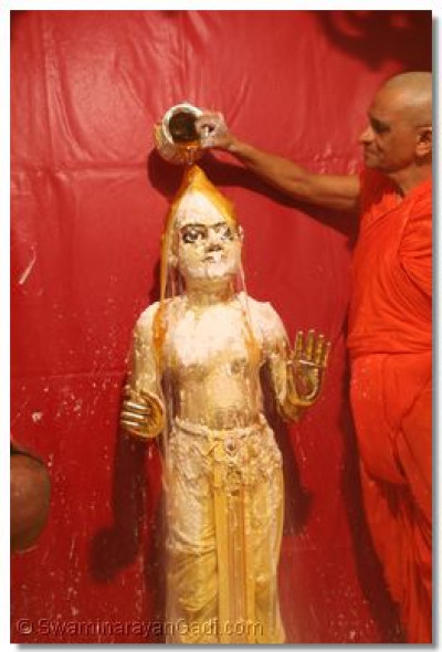 Acharya Swamishree bathes Shree Harikrishna Maharaj with honey