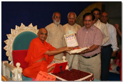 Acharya Swamishree presents awards to outstanding teachers and students of Shree Swaminarayan Arts College
