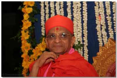 Acharya Swamishree gently smiles as He looks towards the Lord