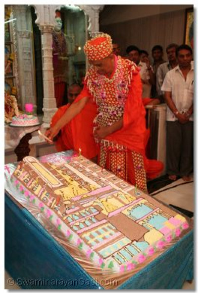 Acharya Swamishree lights candles on the celebrations cake