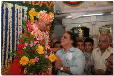Television religious serial director, Shree Moti Sagar, of Ramanand Sagar Pictures, presents flowers to Acharya Swamishree