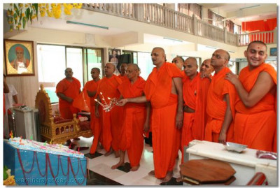 Acharya Swamishree and sants perform Aarti as the Lord dines on the Annakut Thaal