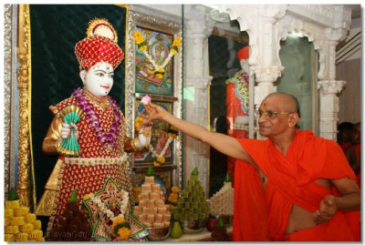 Acharya Swamishree offers a piece of cake to Shree Ghanshyam Maharaj