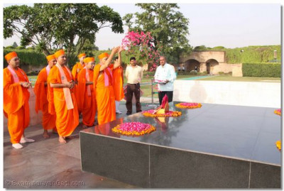 Acharya Swamishree showers the memorial with flower petals