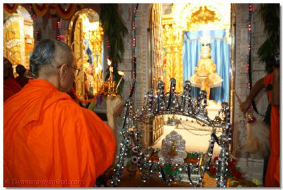 Acharya Swamishree performs Aarti to the Lord seated in the silver, ornate cradle