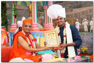 Acharya Swamishree presents an award of commendation to dance choreographer Shree Saurabh Rajyaguru