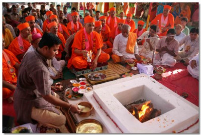The fire is lit, and Acharya Swamishree performs Aarti