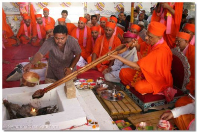 Acharya Swamishree places ghee into the fire