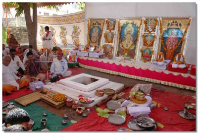 After Acharya Swamishree has commenced the ceremony and departed for the assembly marquee, disciples take part in the Yagna Ceremony