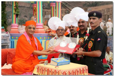 Brigadier Rakeshkumar presents a military ceremonial award to Acharya Swamishree