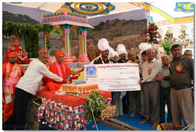Acharya Swamishree and the guests present a charity cheque to Shree Kutchi Leva Patel Samaj – Ahmedabad