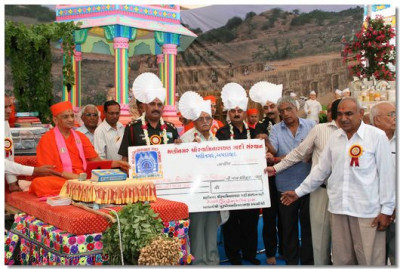 Acharya Swamishree and the guests present a charity cheque to Shree Kutch Baladiya Leva Patel Gnati Vidyalay