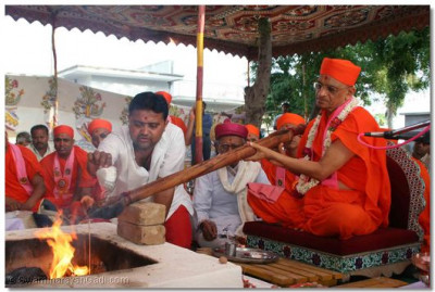 Acharya Swamishree performs the Havan Ceremony and pours ghee into the fire