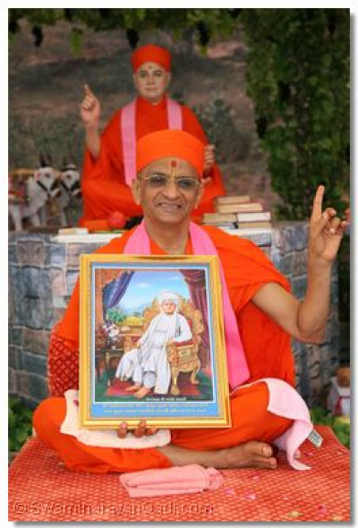 Acharya Swamishree shows the momento of the festival that was given to disciples