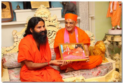 Acharya Swamishree presents a memento to Baba Ramdevji - a photograph of a previous meeting, in Bolton, UK, in 2006