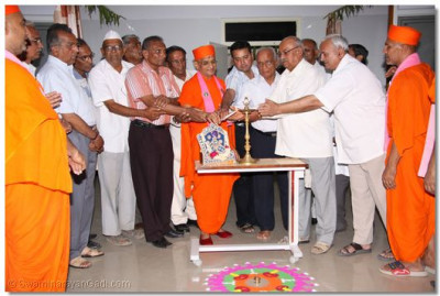 Acharya Swamishree and dignitaries perform the opening with the lighting of a diwo