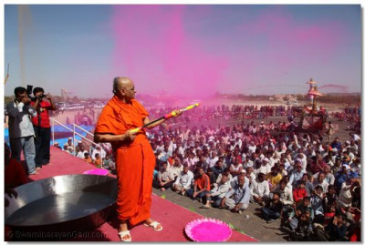 Acharya Swamishree sprays disciples with colours water as coloured powder is released