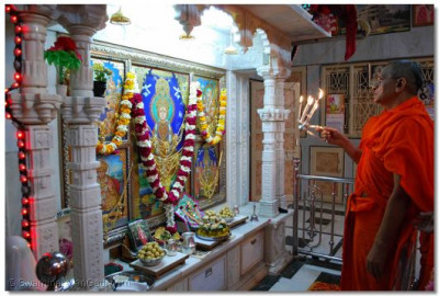 Acharya Swamishree performs aarti to the Lord at the Ladies Temple