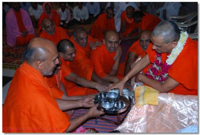 Acharya Swamishree and sants perform the panchamrut ceremony to the Paaduka