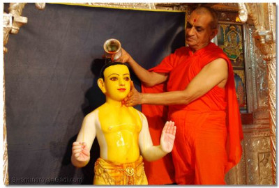 Lord Swaminarayan is bathed in saffron