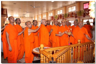 Acharya Swamishree and sants perform aarti to the Lord