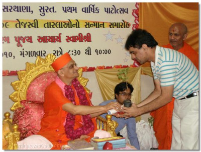 Acharya Swamishree presents a Tulsi plant and prasad to Shree Prafulbhai Pansariya Corporator