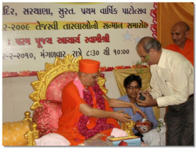 Acharya Swamishree presents a Tulsi plant and prasad to Shree Devchanbhai Kakadiya