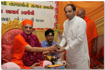 Acharya Swamishree presents a Tulsi plant and prasad to Shree Arjanbhai Dhodakiya, Trustee Ramkrishna Charitable Trust
