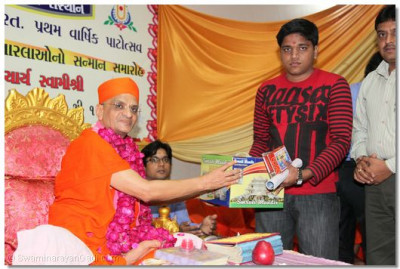 Acharya Swamishree presents a Smruti Mandir memento and prasad to Kapil Anilkumar Tatiya who came 4th in Surat and 40th in allover India in Final C.A. 2009 examinations