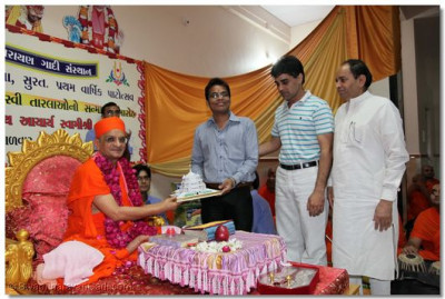 Acharya Swamishree presents a Smruti Mandir memento and prasad to Saurin Mukeshbhai Shah who came 5th in Surat and 45th in allover India in Final C.A. 2009 examinations