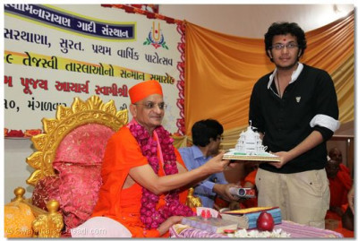Acharya Swamishree presents a Smruti Mandir memento and prasad to Abishek Maheshbhai Mittal who came 6th in Surat and 46th in allover India in Final C.A. 2009 examinations