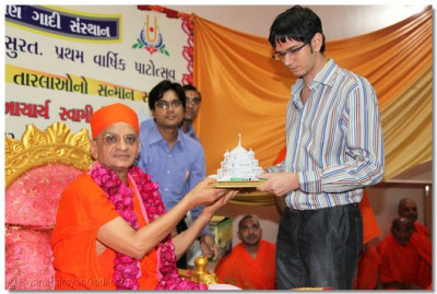 Acharya Swamishree presents a Smruti Mandir memento and prasad to Mehul Rasheshbhai Shah who came 7th in Surat and 49th in allover India in Final C.A. 2009 examinations