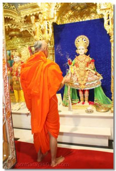 Acharya Swamishree performs aarti to the Lord