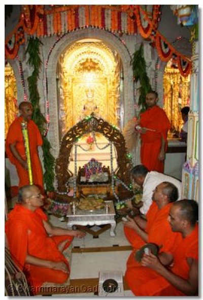 Acharya Swamishree gently swings Shree Harikrishna Maharaj and the sants perform utsav