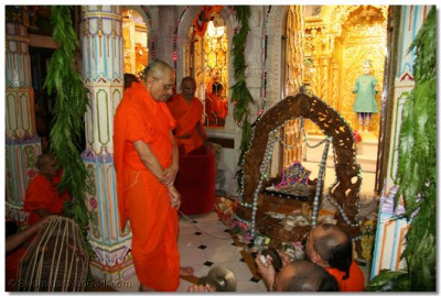 Acharya Swamishree gently swings Shree Harikrishna Maharaj