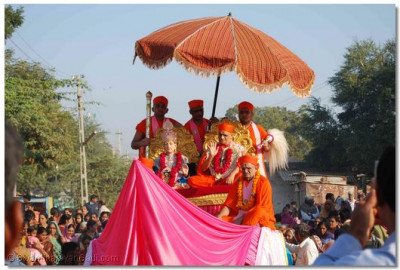Divine darshan of Lord Swaminarayan and Acharya Swamishree in a chariot during a procession in Vamaj