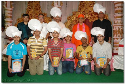 Acharya Swamishree gives darshan to students who received the awards