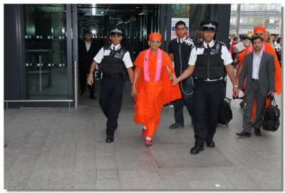 His Divine Holiness Acharya Swamishree is escorted by disciples who are trained Police officers at London's Heathrow Airport