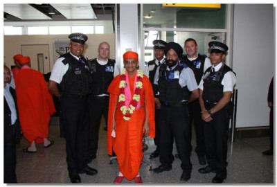 His Divine Holiness Acharya Swamishree gives darshan with all Police officers at London's Heathrow Airport