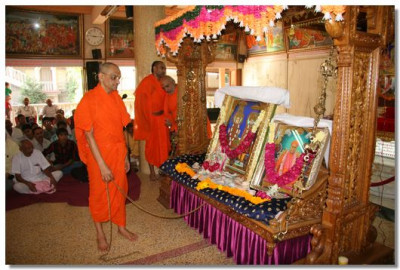 Acharya Swamishree gently sways the swing on which Lord Swaminarayan, Jeevanpran Bapashree, and Jeevanpran Swamibapa are seated