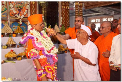 Acharya Swamishree accepts some cake offered by a disciple