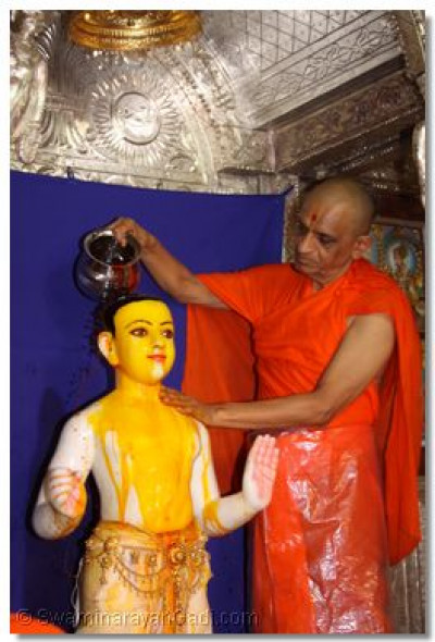 Acharya Swamishree bathes Lord Swaminarayan with saffron