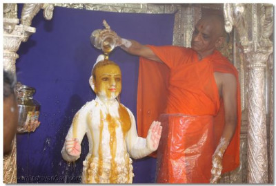 Acharya Swamishree bathes the Lord with honey