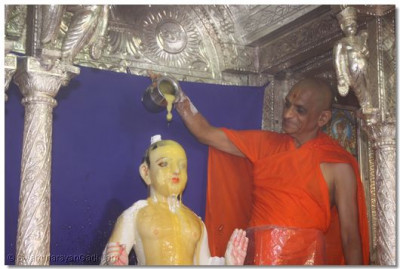 Acharya Swamishree bathes the Lord with ghee