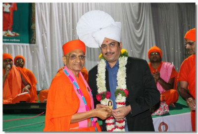 Shree Kaushikbhai Shah receives a paag and memento from Acharya Swamishree