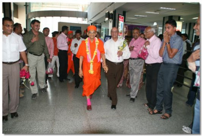 Acharya Swamishree arrives at Ahmedabad airport and is greeted by awaiting disciples