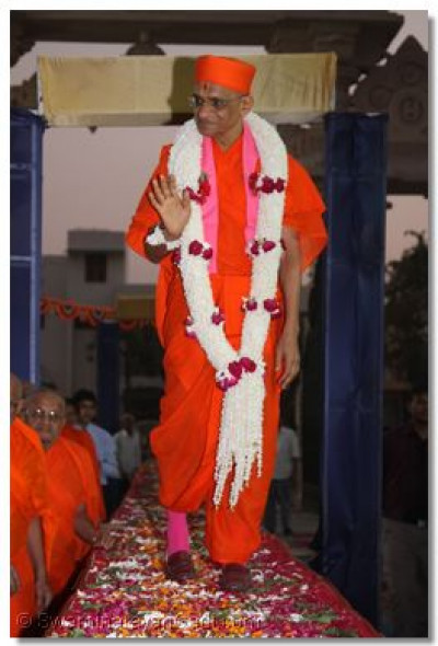 Acharya Swamishree showers His divine blessings to disicples as He walks along a raised platform