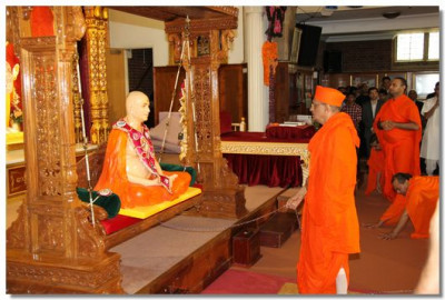 Acharya Swamishree gently swings Jeevanpran Swamibapa who is seated on a large swing