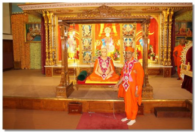 Acharya Swamishree gently swings Jeevanpran Swamibapa seated on a large swing