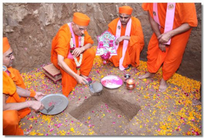 Acharya Swamishree places some mortar in the ground